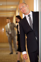 Businessman standing at door while colleagues in background