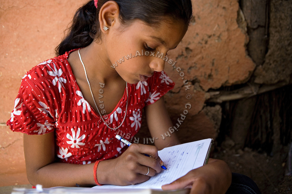 Pooja, 14, a student from the village of Pathpuri, Hoshangabad, Madhya Pradesh, India, taking part to the children's journal, a project launched by Dalit Sangh, an NGO which has been working for the uplift of scheduled castes for the past 22 years, is in her home writing on a notebook provided by the project to the various child reporters. Dalit Sangh is working in collaboration with Unicef India to promote education and awareness within backward communities.