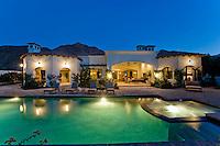 Back yard with illuminated swimming pool dusk