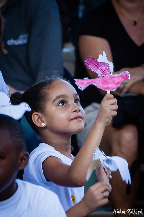 Eleni Bernier, 2nd Grade Lower Elementary class plays with her paper dove of peace.  2012 Peace Day Celebration.  VI Montessori School and International Academy.  21 September 2012.  © Aisha-Zakiya Boyd