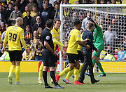 Fan is escorted off the pitch during the Sky Bet Championship match between Watford and Sheffield Wednesday at Vicarage Road, Watford, England on 2 May 2015. Photo by Phil Duncan.