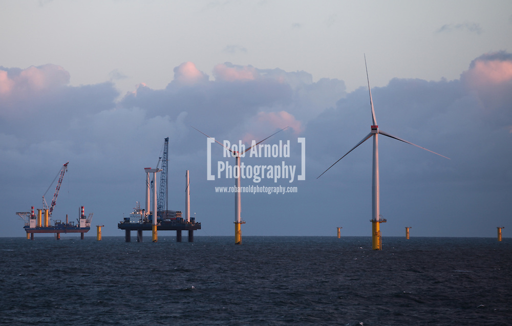22/03/2014. North Wales, UK. The rising sun reflects from the turbines and installation jack up barges on the Gwynt y Môr Offshore Wind Farm off the coast of North Wales this morning, 22nd March 2014. Photo credit : Rob Arnold