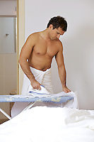 Man in towel ironing clothes on a stand