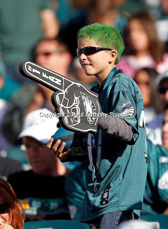 A young fan with green hair waves a foam finger as he cheers for his team during the Philadelphia Eagles NFL week 6 football game against the Atlanta Falcons on Sunday, October 17, 2010 in Philadelphia, Pennsylvania. The Eagles won the game 31-17. (©Paul Anthony Spinelli)