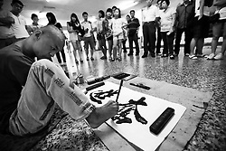 Chinese disabled artist Xi Fu writes the characters 'fen jing' or 'to advance bravely' as a crowd watches in an underground pass in the shopping district of Xidan in Beijing, China 15 June 2013. Few people can master the art of Chinese calligraphy with good functioning hands, much less with their feet. Chinese disabled artist Xi Fu however, made it look like a piece of cake. The 34-year-old whose name meant 'Treasure Happiness' is a common sight in the underground passes of the bustling shopping district of Xidan or tourist walkways of Houhai in Beijing. Passers-by are mesmerize by his skillful display of calligraphic art using only his feet. Xi Fu's story is one that tells of how strong determination and hard work overcame the difficulties of surviving in a society scant with infrastructure and support for the disabled and where they are often discriminated and sidelined.