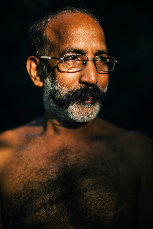 Neriamangalam, India -- February 17, 2018: A portrait of Mr Prakash, part owner of a small toddy shop--which serves home brewed coconut and palm wines--near the Periyar river in Kerala, India.