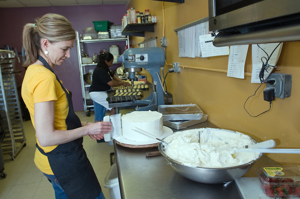 Chef Danni Waldridge, owner of Divinity Fine Catering and Magical Desserts, frosts a Broom's Cake Friday, April 16, 2010 in Louisville, Ky., at her kitchen on Frankfort Avenue. Debbie Handley assists with preparations for a wedding in the background. (Photo by Brian Bohannon)