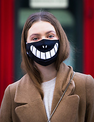 © Licensed to London News Pictures. 16/03/2020. London, UK. A woman commuter wearing a face mask with a smile on walks near Bank in the City of London this morning. New cases and fatalities resulting from the COVID-19 strain of the Coronavirus continue to be reported daily in the UK with major sporting fixtures cancelled and people advised to stay at home if they have a cough and high temperature. Photo credit: Vickie Flores/LNP