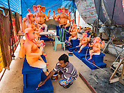 "29 AUGUST 2016 - BANGKOK, THAILAND: Craftsmen at the Vishnu Temple in Bangkok paint a statue of Ganesha, an important Hindu deity known as the ""overcomer of obstacles."" Ganesha Chaturthi is the Hindu festival celebrated on the day of the re-birth of Lord Ganesha, the son of Shiva and Parvati. Ganesha is widely revered as the patron of arts and sciences and the deva of intellect and wisdom. The last day of the festival is marked by the immersion of the deity in nearby bodies of water. The immersion symbolizes the cycle of creation and dissolution in nature. The deities made at the Vishnu Temple in Bangkok will be submerged in rivers and streams across Thailand at several Ganesha festivals held in September.          PHOTO BY JACK KURTZ"