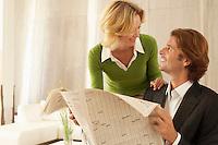 Woman greeting man reading newspaper indoors