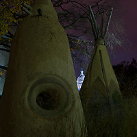 Sculpted teepees stand outside the National Museum of the American Indian in Washington, DC with the glow of the U.S. Capitol Building between them