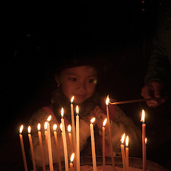 A young girl watches candles being lit by a priest in the Church of the Holy Sepulchre, Jerusalem, Israel.