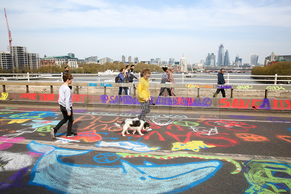 © Licensed to London News Pictures. 18/04/2019. London, UK. Maddy walks her dog on Waterloo Bridge designed by colourful slogans as environmental activists demonstrates for a fourth day of an ongoing climate change protest to demand decisive action from the UK Government on the environmental crisis. Photo credit: Dinendra Haria/LNP