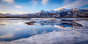 The frozen waters of the Olds River reflecting the surrounding mountains of Kodiak Island, Alaska.