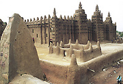 Djenne, Mali. The Grand Mosque. Built in 1905 (Mosque site since 1280) it's the largest mud structure in the world. The wood beams stick out to help climbing when re-covered with mud after the rainy season each year.2005