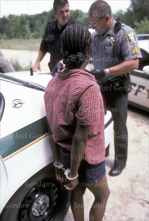 Handcuffed African American juvenile girl, arrested for possession of drugs, officers check for outstanding warrants outside of autos on dirt road in by Putnam County by Sheriff's Office Deputies