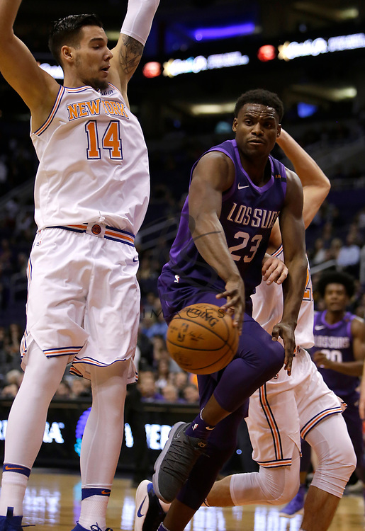 Phoenix Suns forward Danuel House Jr. (23) makes the pass around New York Knicks center Willy Hernangomez in the second half during an NBA basketball game, Friday, Jan. 26, 2018, in Phoenix. The Knicks defeated the Suns 107-85. (AP Photo/Rick Scuteri)
