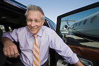 Portrait of senior businessman in front of car.