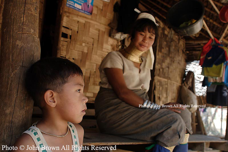 A mother and son who are Karen Paduang refugees from Burma sit on the porch of their home in Ban Nai Soi, Thailand. The Karen people left Burma to flee war atrocities and are considered a tourist attraction by Thailand's government.