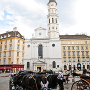 Michaelerkirche, square, and horse-drawn carriage in downtown Vienna, Austria