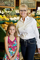 Portrait of a happy senior woman with granddaughter in farmer's market