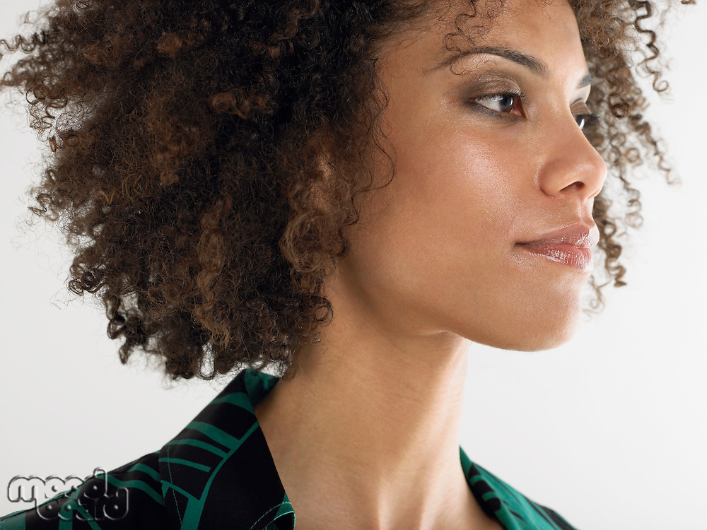 Woman with curly hair head and shoulders in studio