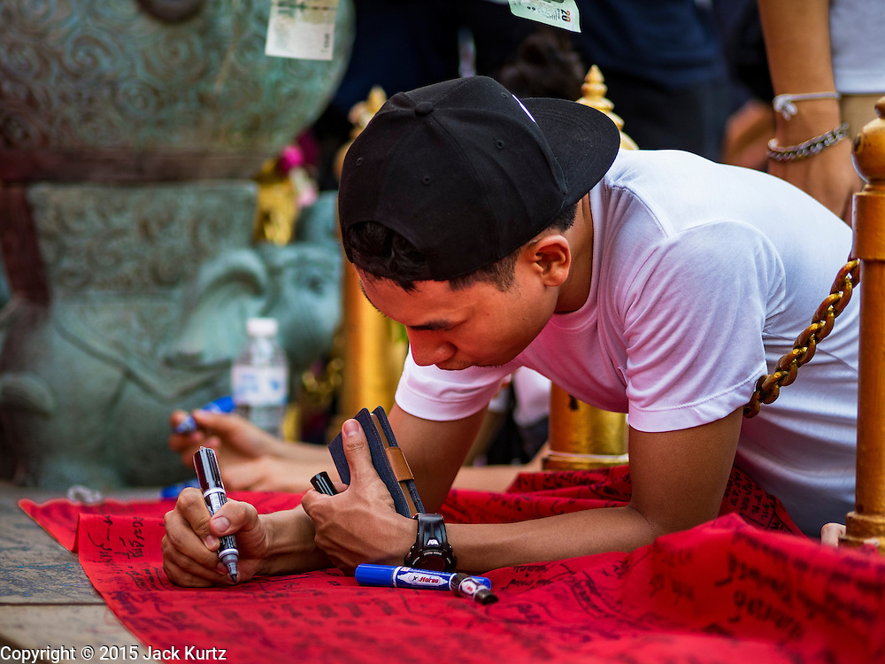 21 NOVEMBER 2015 - BANGKOK, THAILAND: People write prayers on the red cloth wrapped around the chedi at the Wat Saket temple fair. Wat Saket is on a man-made hill in the historic section of Bangkok. The temple has golden spire that is 260 feet high which was the highest point in Bangkok for more than 100 years. The temple construction began in the 1800s in the reign of King Rama III and was completed in the reign of King Rama IV. The annual temple fair is held on the 12th lunar month, for nine days around the November full moon. During the fair a red cloth (reminiscent of a monk's robe) is placed around the Golden Mount while the temple grounds hosts Thai traditional theatre, food stalls and traditional shows.     PHOTO BY JACK KURTZ