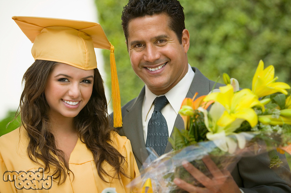 Graduate with flowers and father outside portrait