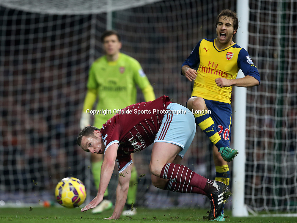 28 December 2014 Premier League Football - West Ham United v Arsenal; Mathieu Flamini of Arsenal reacts to a challenge by Kevin Nolan of West Ham.<br /> Photo: Mark Leech