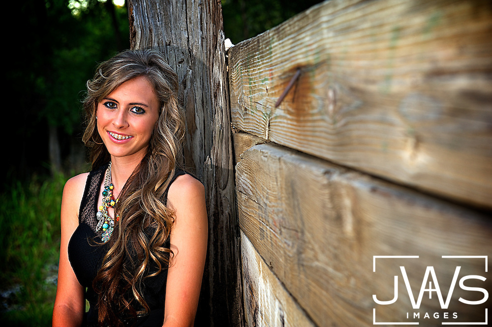 Young lady taking her senior picture in a black dress against a rustic fence post.