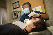 Wesley Murakami, DDS, looks up at x-rays while examining the teeth of a patient who wished to remain unidentified at Justin L Cheng & Wesley Murakami, DDS, in Fremont, California, on April 9, 2014 (Stan Olszewski/SOSKIphoto)