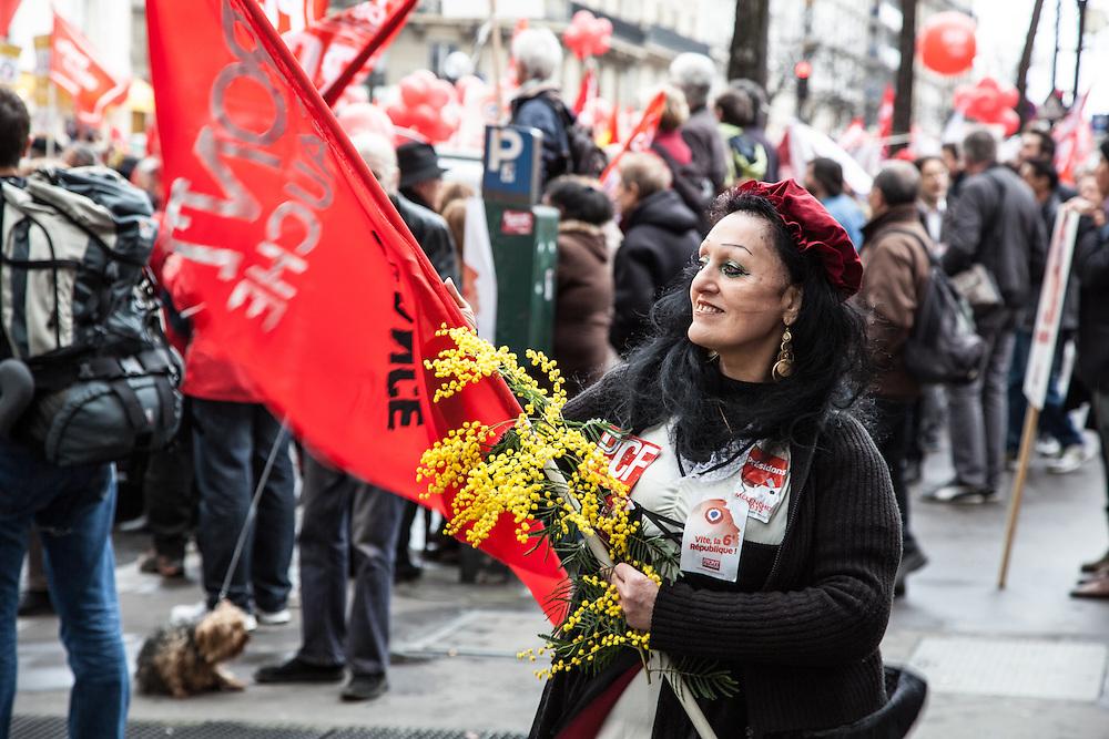 Une femme agite un drapeau rouge en tenant une branche de mimosa, Place de la République le 18 mars 2012 à 13h, avant le départ du cortège du Front de Gauche vers la Bastille.
