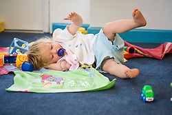 Baby at Nursery School; rolling around on the floor,