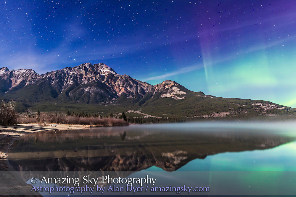 An aurora display appears to the right of Pyramid Mountain and over Pyramid Lake, in Jasper National Park, Alberta on Oct 24/25, 2015. This is one frame from a 600-frame time-lapse sequence. Exposure was 15 seconds at f/4 and ISO 800 in the bright moonlight, with the Nikon D750 and 24mm Sigma lens.