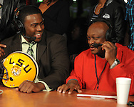 Lafayette High quarterback Jeremy Liggins (left) jokes with host Fred Johnson during the Collier Dental Sports Roundup at the Irie in Oxford, Miss. on Monday, January 30, 2012.