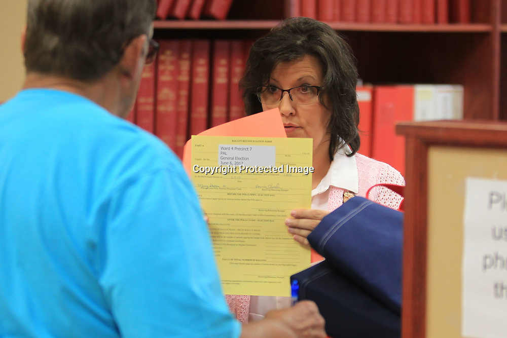 Missy Shelton, Deputy City Clerk for Tupelo, goes over the ballot reconciliation form with Ronnie Shurden, the returning and receiving manager for the ward 4, precint 7 poll location. Poll workers came to the city clerks office to pick up their precint bags for Tuesday's election.