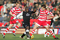 Photo: Paul Thomas.<br /> Doncaster Rovers v Swansea City. Coca Cola League 1. 17/02/2007.<br /> <br /> Adebayo Akinfenwa (C) of Swansea tries to beat Graeme Lee (R) and Adam Lockwood (L).