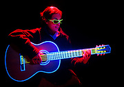 Young girl playing glowing guitar.Black light