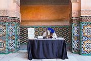 A calligrapher works at a stall infront of traditional Moroccan zellige mosaic work - Islamic, geometric mosaic patterns - lining the walls of the Ali Ben Youssef Medersa, Marrakesh