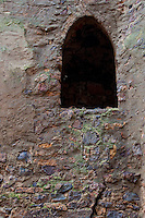 Detail of an ancient castle tower wall with darkened arched window near Leipzig, Germany.  Detail shows the different colors of the stones in the wall.