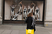 Woman passing a window of Agent Provocateur - lingerie products - in Selfridges, Oxford street, London.