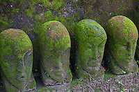 A line of green mossy stone carved heads in Batubulan, Bali, Indonesia