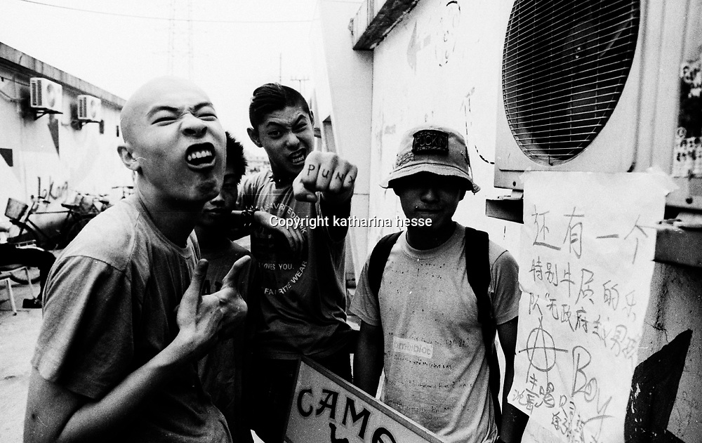 "BEIJING, HAIDIAN DISTRICT, CHINA - AUGUST 15: Tu Qiang (L) and Shen Yue (C) of ""Anarchy Boys"" and Li Punk hang out together before a punk show August 15, 1999 in the Haidan district of Beijing, China. In the spring of 1998, a handful of youngsters teamed up to unofficially rebel against conformist Chinese life. They shaved their heads, and founded bands with names like ""Brain Failure"" and ""Anarchy Boys."" Although the majority of the punks came from well-off families, they preferred to live in self-imposed poverty. The Scream Bar and its surrounding dusty alleyways in the student district became the center of youthful rebellion until it was finally closed in 2000. The punks bands have moved on to other bars in Beijing, some received contracts with foreign record companies and even toured in Europe, Japan and the U.S."