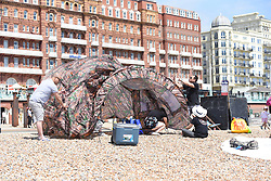 © Licensed to London News Pictures. 27/05/2020. Brighton, UK. Members of the public erect a tent on the beach at Brighton, East Sussex, during lockdown to prevent to spread of COVID-19.  Photo credit: Liz Pearce/LNP