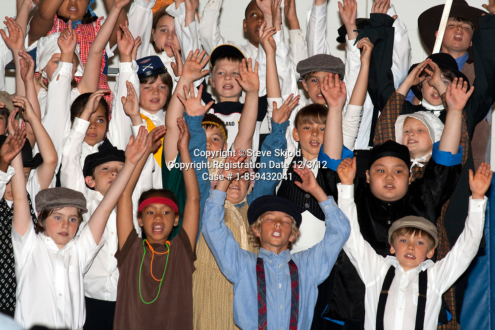 Exuberant school singers age 10 with arms over head in historic Minnesota costumes. Horace Mann School. St Paul Minnesota MN USA