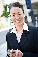Portrait of young businesswoman with mobile and bluetooth