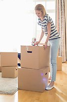 Woman packing cardboard box at home
