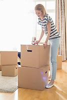 Woman packing cardboard box at home