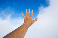 A bare arm and hand reaching upward toward blue sky and clouds.