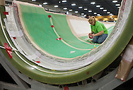 Sheri Vantsant tapes down a vacuum tube as they prepare a wind turbine blade at TPI Composites in Newton, Iowa on February 12, 2010.